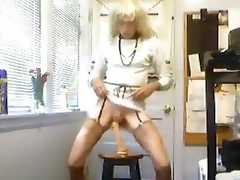 Denise Adams crossdresser plays adjacent to a dildo